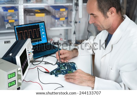 Senior male tech works in hardware repair facility - stock photo