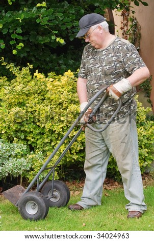 senior male using a trolley cart outside - stock photo