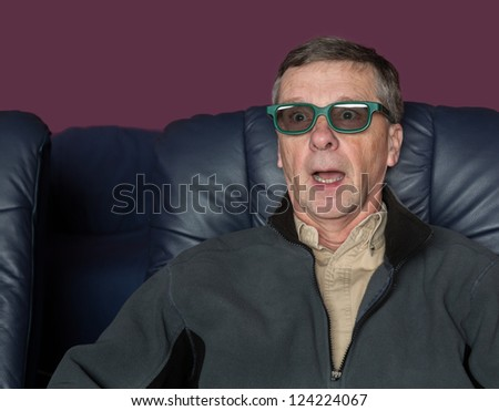Senior male with shocked expression watching movie in home theater in 3d glasses - stock photo