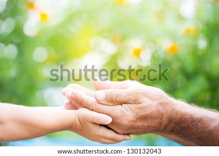 Senior man and baby holding empty hands against green spring background - stock photo