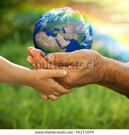 Senior man and baby holding the Earth in hands against a rainbow in spring. Elements of this image furnished by NASA - stock photo