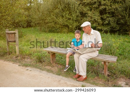 Senior man and cute child reading a newspaper sitting on park bench. Two different generations concept. - stock photo