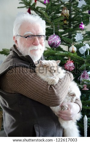 senior man and his cat in front of noel tree in living room - stock photo
