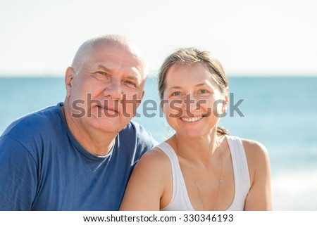 senior man and mature woman together against sea - stock photo