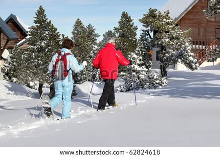Senior man and senior woman snowshoeing back to snow - stock photo