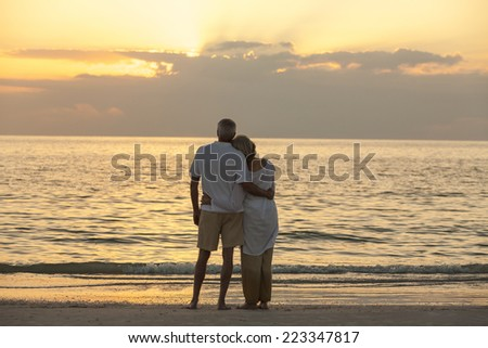 Senior man and woman couple embracing at sunset or sunrise on a deserted tropical beach  - stock photo