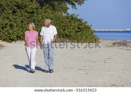 Senior man and woman couple holding hands walking on a deserted beach  - stock photo