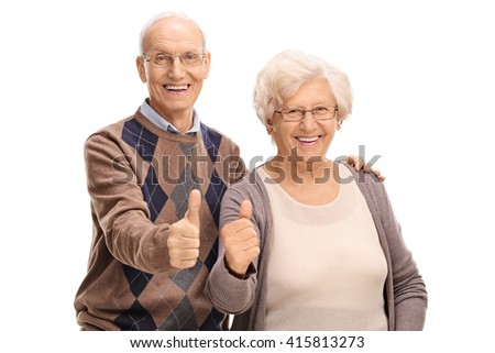 Senior man and woman giving thumbs up and looking at the camera isolated on white background - stock photo