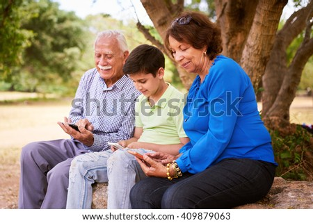 Senior man and woman learning internet and mobile phones: young kid helping his grandparents surfing the web with their new mobile phones. All people hold a phablet and type on screen - stock photo