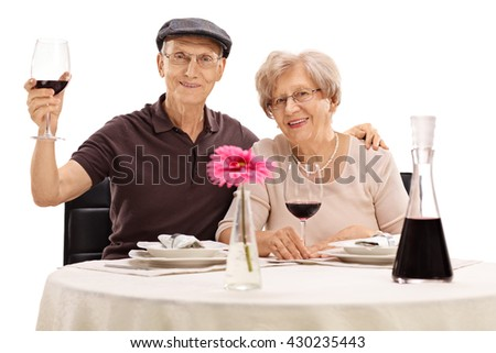 Senior man and woman posing seated at a dinner table with red wine isolated on white background - stock photo