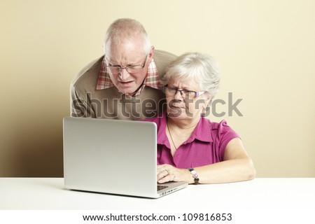 Senior man and woman using laptop whilst looking confused - stock photo