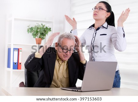 Senior man and young woman having problem in the office. Both holding head with raised arms - stock photo