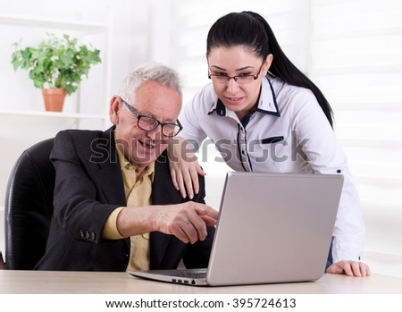 Senior man and young woman smiling and looking at laptop in the office - stock photo