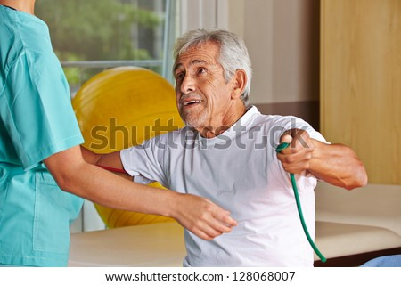 Senior man at rehab with nurse pulling on a string - stock photo