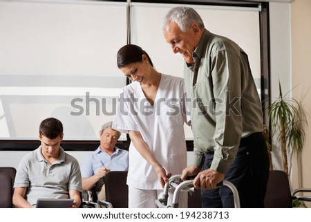 Senior man being assisted by female nurse to walk the Zimmer frame with people sitting in background - stock photo