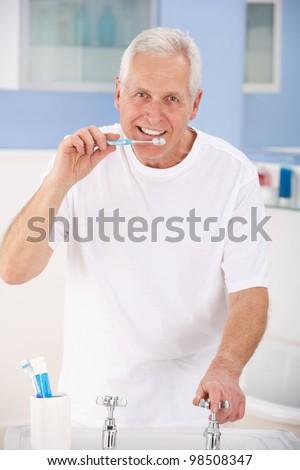 Senior man brushing teeth - stock photo