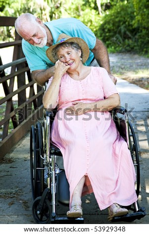 Senior man caring for his disabled wife in wheelchair. - stock photo