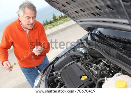 Senior man checking car motor levels - stock photo