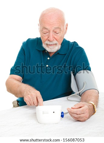 Senior man checking his blood pressure at home.  Isolated on white.   - stock photo