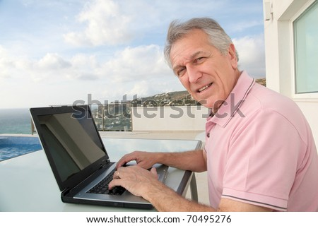 Senior man connected on internet outside the house - stock photo