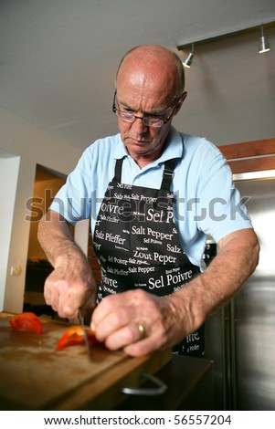 Senior man cutting a red pepper - stock photo