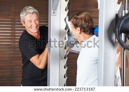 Senior man doing back training at barbell in a gym - stock photo