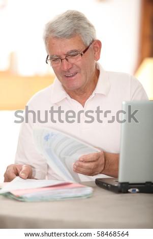 Senior man doing tax return on internet - stock photo