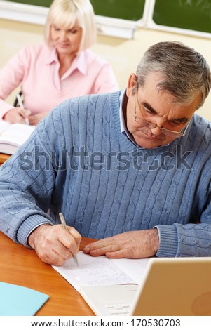 Senior man doing the task in classroom with his classmate on background - stock photo