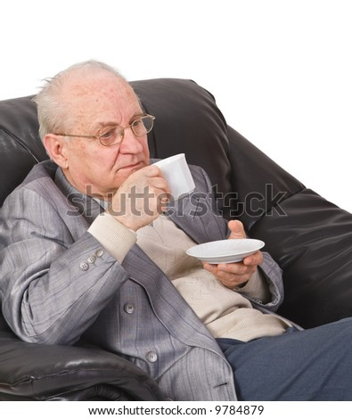 Senior man drinking a cup of tea in his office armchair. - stock photo