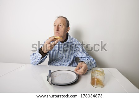 Senior man eating bread spread with sweet jelly jam at table - stock photo