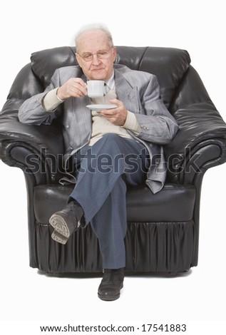 Senior man enjoying a cup of tea in his office armchair. - stock photo