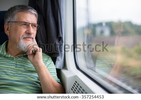 Senior man enjoying a train travel - leaving his car at home, he savours the time spent travelling, looks out of the window, has time to admire the landscape passing by - stock photo