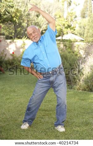 Senior Man Exercising In Garden - stock photo