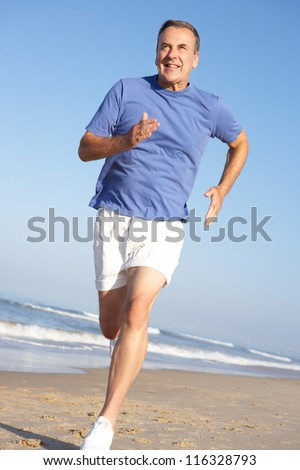 Senior Man Exercising On Beach - stock photo
