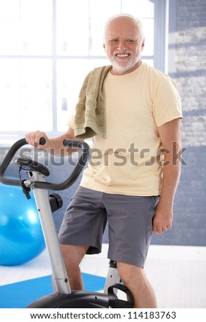 Senior man exercising on fitness cycle, smiling. - stock photo