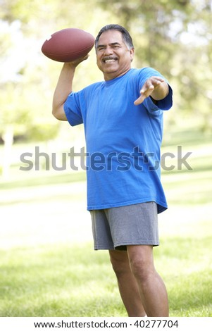 Senior Man Exercising With American Football In Park - stock photo