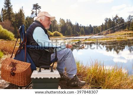 Senior man fishing in a lake, Big Bear, California, close-up - stock photo