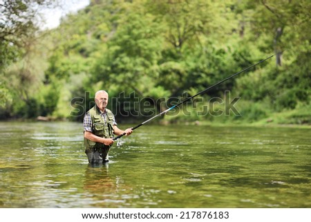 Senior man fishing in a river on a sunny summer day  - stock photo