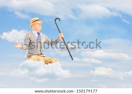 Senior man floating on a cloud and spreading arms while holding a cane against cloudy sky - stock photo