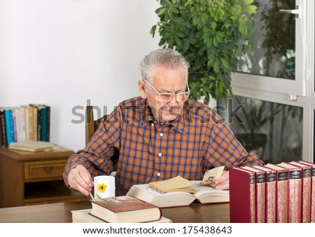 Senior man found newspaper clipping in old books - stock photo