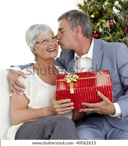 Senior man giving a kiss and a Christmas present to his wife at home - stock photo