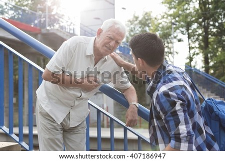 Senior man has pain in heart on stairs - stock photo