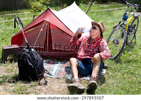 Senior man hiker drinking water and resting in front of tent after bike ride - stock photo