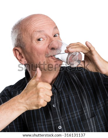 Senior man holding a glass of water and giving a thumb up on a white background - stock photo