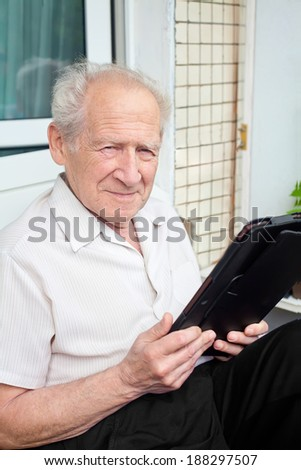 senior man holding a touchpad PC in his hands - stock photo