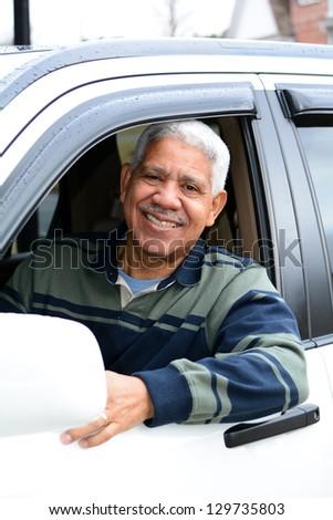 Senior man holding up keys to his new car - stock photo