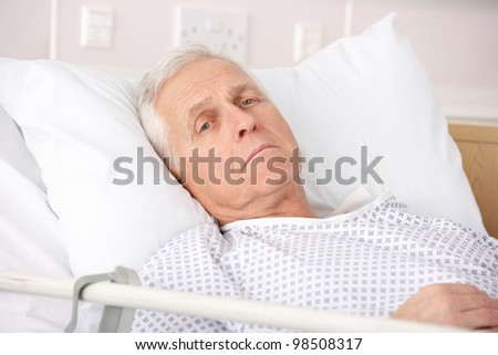 Senior man ill in hospital bed - stock photo