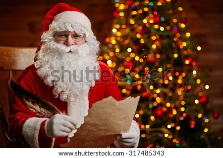 Senior man in costume of Santa Claus holding feather and Christmas letter - stock photo