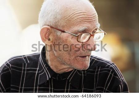 Senior man in eyeglasses looking sideways outdoor portrait - stock photo