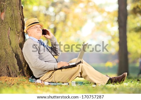 Senior man in park talking on a mobile phone and working on laptop - stock photo